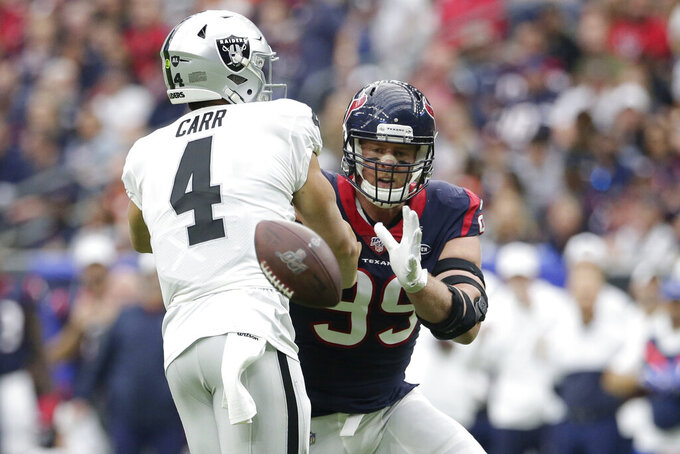 Houston Texans defensive end J.J. Watt (99) blocks a pass by Oakland Raiders quarterback Derek Carr (4) during the first half of an NFL football game Sunday, Oct. 27, 2019, in Houston. (AP Photo/Michael Wyke)