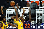 Golden State Warriors forward Andrew Wiggins (22) drives against Phoenix Suns center Deandre Ayton (22) during the first half of an NBA basketball game, Thursday, March 4, 2021, in Phoenix. (AP Photo/Rick Scuteri)