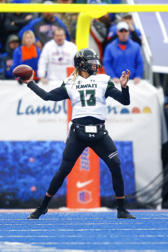 Hawaii quarterback Cole McDonald (13) looks to throw the ball against Boise State during the first half of an NCAA college football game for the Mountain West Championship Saturday, Dec. 7, 2019, in Boise, Idaho. (AP Photo/Steve Conner)