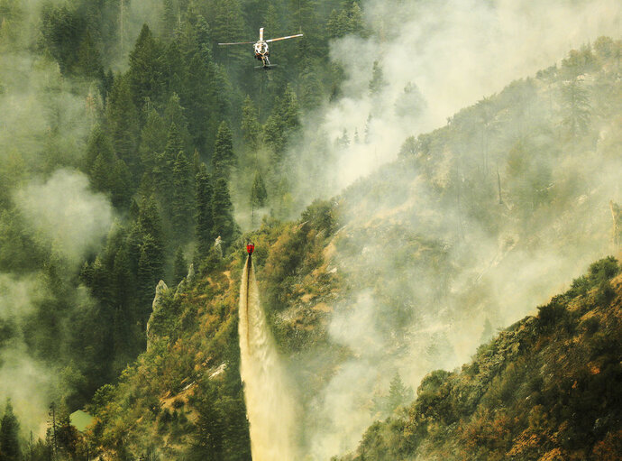 A helicopter drops water on the Pole Creek fire in Woodland Hills, Utah, on Friday, Sept. 14, 2018. Sparked by lightning in a remote, forested area on Sept. 6, the fire raged out of control as high winds kicked up Thursday. (Jeffrey D. Allred/The Deseret News via AP)