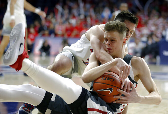 Arizona guard Alex Barcello and Washington State forward Aljaz Kunc, front, scramble for the ball during the second half of an NCAA college basketball game Saturday, Feb. 9, 2019, in Tucson, Ariz. Washington State won 69-55. (AP Photo/Rick Scuteri)