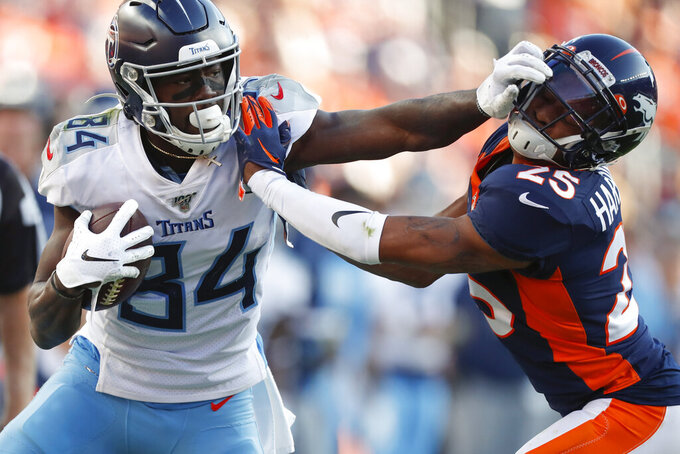 Tennessee Titans wide receiver Corey Davis, left, pushes off Denver Broncos cornerback Chris Harris during the second half of an NFL football game Sunday, Oct. 13, 2019, in Denver. (AP Photo/David Zalubowski)