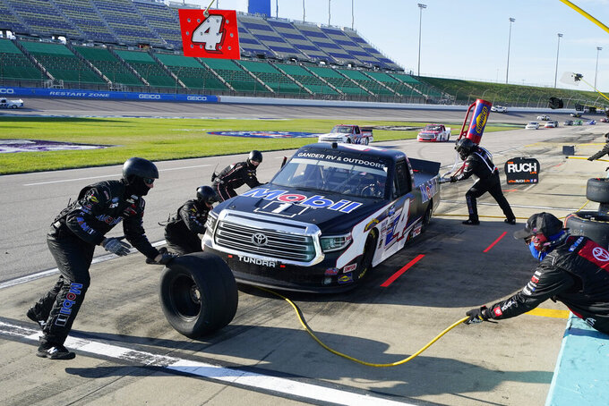 Raphael Lessard (4) makes a pit stop during a NASCAR Truck Series auto race at Kansas Speedway in Kansas City, Kan., Friday, July 24, 2020. (AP Photo/Charlie Riedel)