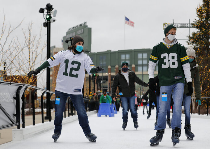 Spectators skate at a local rink next to Lambeau Field before an NFL divisional playoff football game between the Los Angeles Rams and Green Bay Packers, Saturday, Jan. 16, 2021, in Green Bay, Wis. (AP Photo/Mike Roemer)