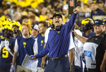 Michigan coach Jim Harbaugh signals a Michigan first down on the sideline during the fourth quarter of the team's NCAA college football game against Washington in Ann Arbor, Mich., Saturday, Sept. 11, 2021. (AP Photo/Tony Ding)