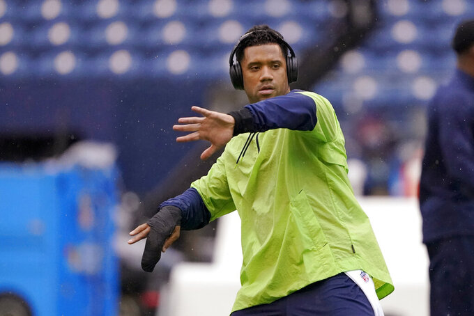 Seattle Seahawks injured quarterback Russell Wilson goes through a throwing motion on the field before an NFL football game against the New Orleans Saints, Monday, Oct. 25, 2021, in Seattle. (AP Photo/Ted S. Warren)