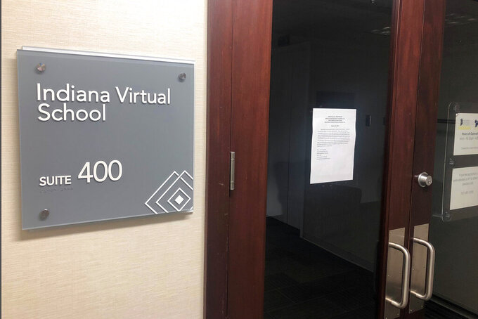 FILE- In a Sept. 13, 2019 file photo the closed office of Indiana Virtual School, in Indianapolis, is seen with a message to creditors taped to the door stating that it no longer had assets or bank accounts. The leaders of two now-closed Indiana online charter schools are accused in a new lawsuit of defrauding the state of more than $150 million by padding their student enrollments and inappropriately paying money to web of related businesses. (AP Photo/Tom Davies, File)