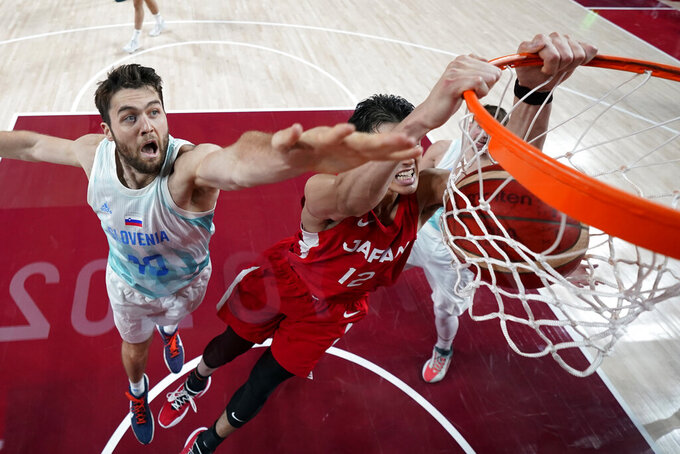 Japan' Yuta Watanabe (12) scores past Slovenia's Mike Tobey (10) during a men's basketball game at the 2020 Summer Olympics, Thursday, July 29, 2021, in Saitama, Japan. (AP Photo/Eric Gay)