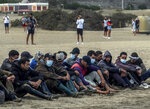 Migrants from Morocco sit on a beach after arriving at the coast of the Canary Island, crossing the Atlantic Ocean sailing on a wooden boat on Tuesday, Oct.20, 2020. Some 1,000 migrants have spent the night again sleeping in emergency tents in a dock while authorities in the Canary Islands complain that the Spanish government keeps blocking transfers of newly arrived migrants to the mainland over coronavirus concerns. (AP Photo/Javier Bauluz)
