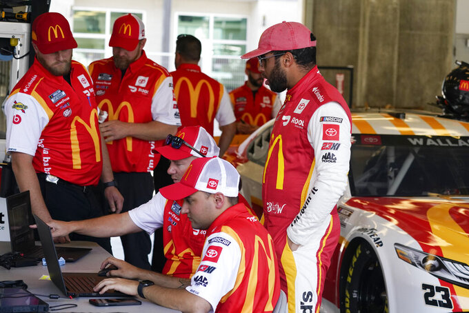 Bubba Wallace talks with his crew during practice for a NASCAR Cup Series auto race at Indianapolis Motor Speedway, Saturday, Aug. 14, 2021, in Indianapolis. (AP Photo/Darron Cummings)