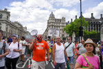 People gather outside the Palace of Westminster, to protest against the delay of the planned relaxation of lockdown measures, in London, Monday, June 14, 2021. British Prime Minister Boris Johnson is expected to confirm Monday that the next planned relaxation of coronavirus restrictions in England will be delayed as a result of the spread of the delta variant first identified in India. (AP Photo/Alberto Pezzali)