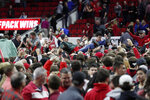 North Carolina State fans storm the court following the team's win over Duke in an NCAA college basketball game in Raleigh, N.C., Wednesday, Feb. 19, 2020. (AP Photo/Gerry Broome)
