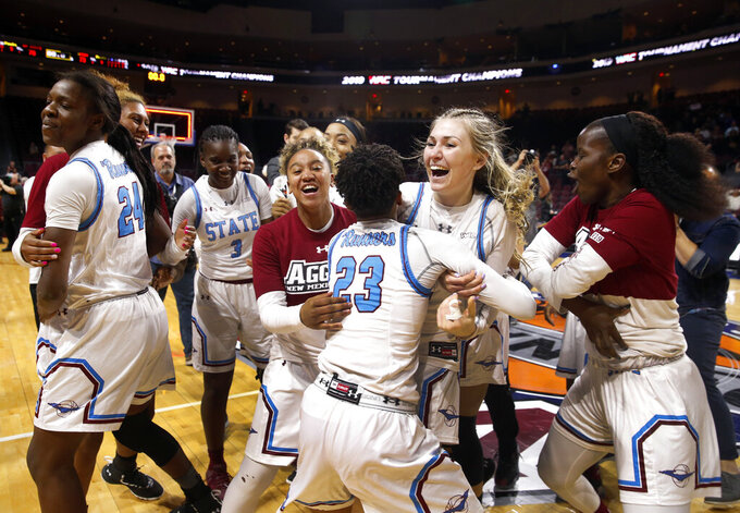 New Mexico State players celebrate after beating Texas-Rio Grande Valley 76-73 in double overtime during a NCAA college basketball Western Athletic Conference Women's Tournament championship game Saturday, March 16, 2019, in Las Vegas. New Mexico State guard Aaliyah Prince (23) and teammate Brooke Salas (2) hug at center. (AP Photo/Steve Marcus)