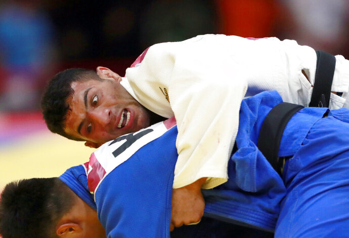 FILE - In this Thursday, Aug. 30, 2018 file photo, Saeid Mollaei of Iran, top, competes against Didar Khamza of Kazakhstan during their men's - 81kg final judo match at the18th Asian Games in Jakarta, Indonesia. Judo world champion Iran has been banned from international judo competitions for refusing to let its athletes fight Israeli opponents. The International Judo Federation has imposed an indefinite ban on Iran's team until it promises to end a long-running boycott of Israel. (AP Photo/Tatan Syuflana, File)