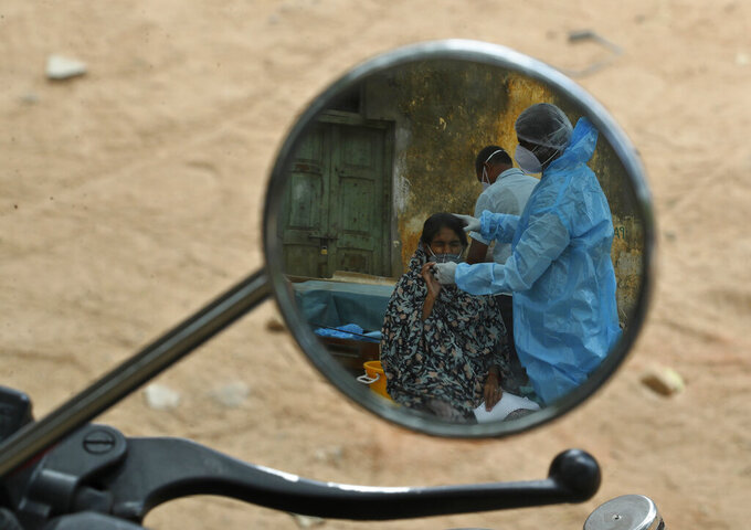 A health worker takes a nasal swab sample of a woman to test for COVID-19 are reflected in a mirror of a motorcycle in Hyderabad, India, Friday, May 7, 2021. With coronavirus cases surging to record levels, Indian Prime Minister Narendra Modi is facing growing pressure to impose a harsh nationwide lockdown amid a debate whether restrictions imposed by individual states are enough. (AP Photo /Mahesh Kumar A.)