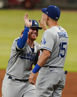 Los Angeles Dodgers' Justin Turner, left, high-fives Austin Barnes, right, after they defeated the Atlanta Braves in a baseball game Friday, June 4, 2021, in Atlanta. (AP Photo/Brynn Anderson)