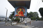In this Nov. 17, 2019, photo, commuters walk past a statue of Buddha in Kandy, Sri Lanka. In this mountain city that was for centuries home to Sri Lanka's kings and in recent years has been riven by religious violence, Buddhist nationalists are rejoicing the election of the country's newest leader. They hope he ushers in another golden era for the nation's ethnic majority. Buddhist nationalism has been on the rise, and it was thrust to the forefront of Sri Lankan politics after Islamic State-inspired suicide attacks by local militants killed 269 people at churches and hotels on Easter Sunday. (AP Photo/Dar Yasin)