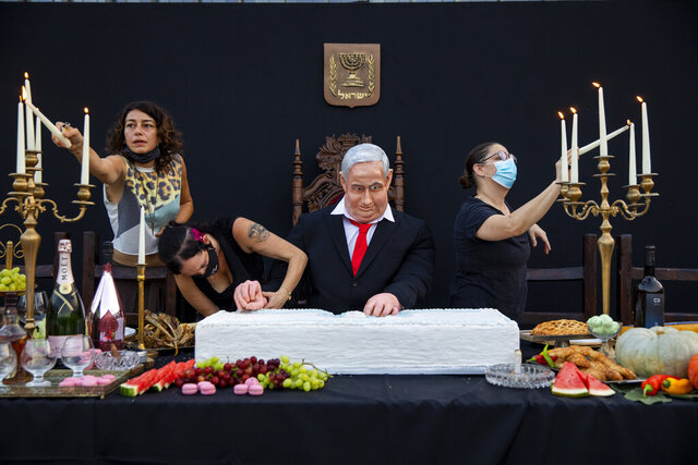 Team members of Israeli artist Itay Zalait, work on an installation depicting Prime Minister Benjamin Netanyahu at a mock