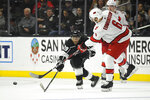 Carolina Hurricanes defenseman Joel Edmundson, right, passes the puck past Los Angeles Kings left wing Alex Iafallo during the second period of an NHL hockey game Tuesday, Oct. 15, 2019, in Los Angeles. (AP Photo/Mark J. Terrill)