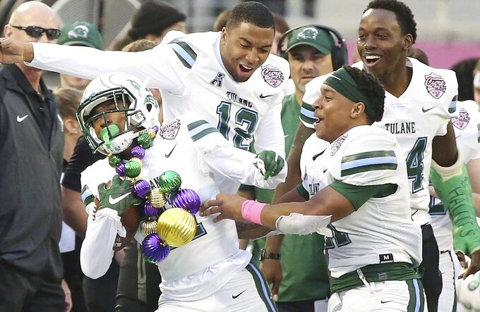 Tulane defensive back Chris Joyce (wearing ornament necklace) celebrates with teammates after an interception during the Cure Bowl NCAA college football game against Louisiana in Orlando, Fla, on Saturday, Dec. 15, 2018. (Stephen M. Dowell/Orlando Sentinel via AP)
