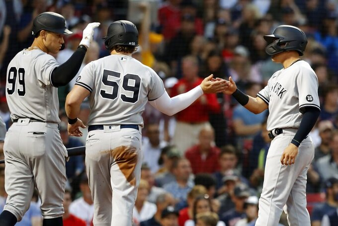 New York Yankees' Gio Urshela, right, celebrates after scoring with Luke Voit (59) on a two-run single by DJ LeMahieu during the second inning of a baseball game against the Boston Red Sox, Friday, June 25, 2021, in Boston. (AP Photo/Michael Dwyer)