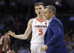 Virginia head coach Tony Bennett, right, talks with Kyle Guy (5) during the first half of an NCAA college basketball game against Florida State in the Atlantic Coast Conference tournament in Charlotte, N.C., Friday, March 15, 2019. (AP Photo/Nell Redmond)