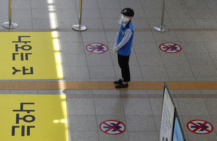An employee wearing a face mask and face shield stands to guide passengers to maintain a one-way walk flow as a precaution against the coronavirus at the Seoul Railway Station in Seoul, South Korea, Thursday, Sept. 10, 2020. (AP Photo/Lee Jin-man)
