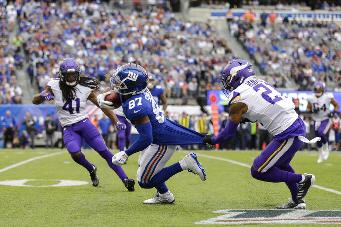 New York Giants wide receiver Sterling Shepard (87) is brought down by Minnesota Vikings cornerback Mike Hughes (21) during the third quarter of an NFL football game, Sunday, Oct. 6, 2019, in East Rutherford, N.J. (AP Photo/Adam Hunger)