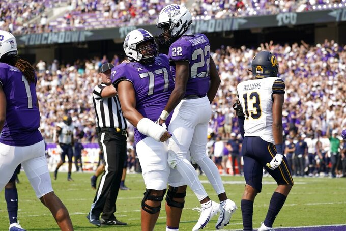 TCU offensive tackle Brandon Coleman (77) and wide receiver Blair Conwright (22) celebrate after Conwright caught a pass for a touchdown as California's Miles Williams (13) walks past in the first half of an NCAA college football game in Fort Worth, Texas, Saturday, Sept. 11, 2021. (AP Photo/Tony Gutierrez)