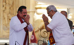 Sri Lanka's former President Mahinda Rajapaksa, left, greets his younger brother, President Gotabaya Rajapaksa, after being sworn in as the prime minister at Kelaniya Royal Buddhist temple in Colombo, Sri Lanka, Sunday, Aug. 9, 2020. (AP Photo/Eranga Jayawardena)