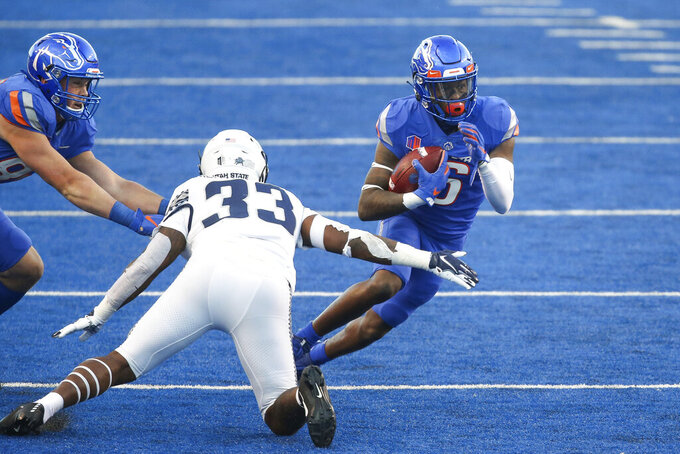 Boise State wide receiver Ct Thomas (6) runs after a catch as Utah State linebacker Kevin Meitzenheimer (33) reaches out in the first half in an NCAA college football game Saturday, Oct. 24, 2020, in Boise, Idaho. (AP Photo/Steve Conner)