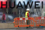 Workers clean the front of the new Huawei flagship store due to open soon in Madrid, Spain, Wednesday, May 22, 2019. The Trump administration sanctions against Huawei have begun to bite even though their dimensions remain unclear. U.S. companies that supply the Chinese tech powerhouse with computer chips face a drop in sales, and Huawei's smartphone sales could get decimated with the anticipated loss of Google's popular software and services. (AP Photo/Paul White)