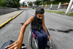 A man wearing a protective face mask hitches a ride in his wheelchair by grabbing on to the back of a motorcycle, near the Miraflores Palace in Caracas, Venezuela, Saturday, Aug. 8, 2020, amid the new coronavirus pandemic. (AP Photo/Matias Delacroix)