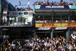 In this March 17, 2019, file photo, the award ceremony for the Australian Formula 1 Grand Prix is watched by team supporters while Mercedes driver Valtteri Bottas of Finland, teammate Lewis Hamilton of Britain and Red Bull driver Max Verstappen of the Netherlands stand on the podium in Melbourne, Australia. The start of the 2021 Formula One season has been delayed after the Australian Grand Prix was postponed because of the coronavirus pandemic. The Australian race in Melbourne has been rescheduled from March 21 to November 21. (AP Photo/Rick Rycroft, File)