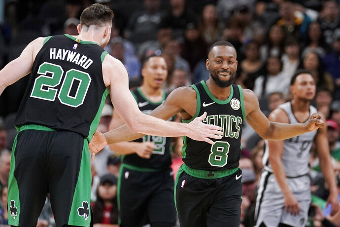 Boston Celtics' Kemba Walker (8) and Gordon Hayward celebrate a basket during the first half of an NBA basketball game against the San Antonio Spurs, Saturday, Nov. 9, 2019, in San Antonio. (AP Photo/Darren Abate)