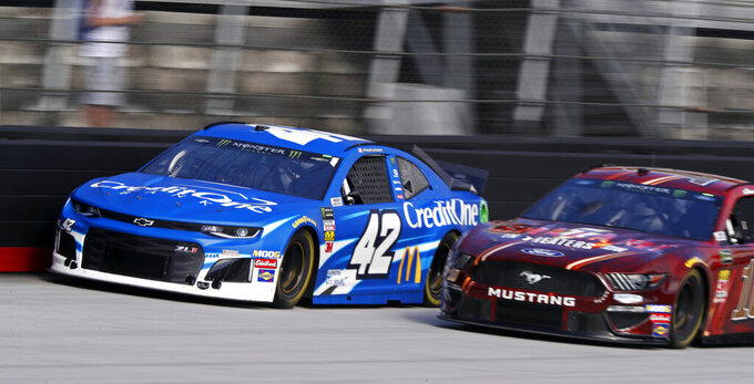 Driver Kyle Larson (42) races with Aric Almirola (10) during practice for a NASCAR Cup Series auto race, Saturday, April 6, 2019, in Bristol, Tenn. (AP Photo/Wade Payne)