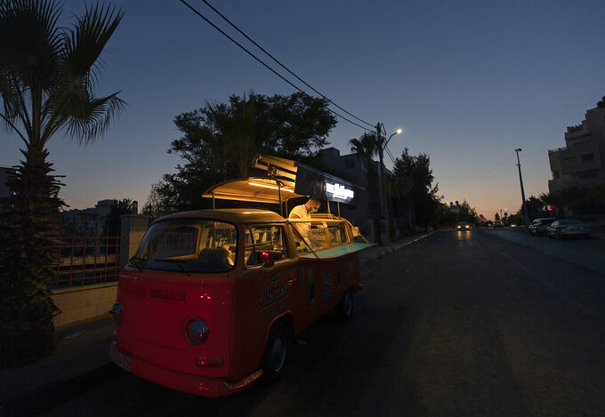 A man sells hot dogs and beverages out of a converted van in the West Bank city of Ramallah, Wednesday, Sept. 23, 2020. With dine-in restaurants mostly closed due to health restrictions, food trucks have allowed entrepreneurial Palestinian businessmen to find a way to keep working(AP Photo/Nasser Nasser)