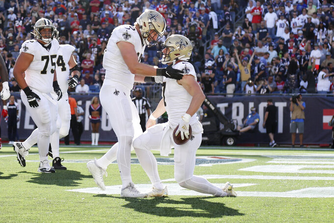 New Orleans Saints quarterback Taysom Hill, right, is congratulated by tight end Garrett Griffin (45) after his touchdown during the second half of an NFL football game against the New England Patriots, Sunday, Sept. 26, 2021, in Foxborough, Mass. (AP Photo/Mary Schwalm)
