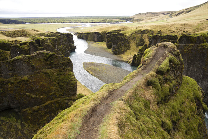 This photo taken Wednesday, May 1, 2019, shows a cliff at the Fjadrárgljúfur canyon in southeastern Iceland. The canyon area has suffered environmental damages after intense traffic, prompted by the music video
