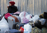 A Syrian refugee cries next to her belongings as she waits to board a bus to take her home to Syria, in Beirut, Lebanon, Tuesday, Dec. 3, 2019. Hundreds of Syrian refugees have headed home in the first batch to leave Lebanon since protests broke out more than a month ago. Lebanon is hosting some 1 million Syrian refugees who fled their country after the war broke out eight years ago. (AP Photo/Hussein Malla)