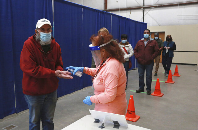 Dell Weston, left, holds out his hands to receive hand sanitizer from a poll worker at the fair grounds early voting center on Saturday, Oct. 17, 2020, in Santa Fe, N.M. Weston, a retired artist and metalworker, said he's a Republican plans to vote for Trump. He came for a sample ballot so that he could research down-ballot candidates and issues before he votes in person in the coming weeks. (AP Photo/Cedar Attanasio)