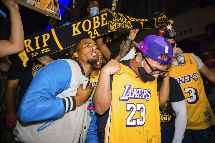 Fans celebrate, Sunday, Oct. 11, 2020, in Los Angeles, after the Los Angeles Lakers defeated the Miami Heat in Game 6 of basketball's NBA Finals to win the championship. (AP Photo/Jintak Han)