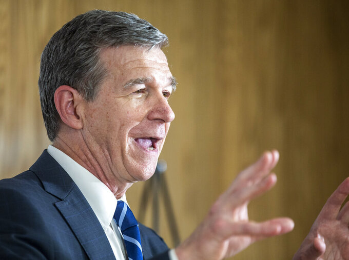 North Carolina Gov. Roy Cooper speaks to the gathered media after his tour of a COVID-19 vaccine clinic at the Pine Hall Brick plant in Madison, N.C., on Thursday, May 27, 2021. (Woody Marshall/News & Record via AP)