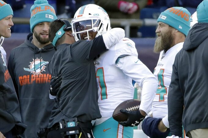 Miami Dolphins cornerback Eric Rowe receives congratulations on the sideline after returning an interception of a Tom Brady pass for a touchdown in the first half of an NFL football game against the New England Patriots, Sunday, Dec. 29, 2019, in Foxborough, Mass. (AP Photo/Elise Amendola)
