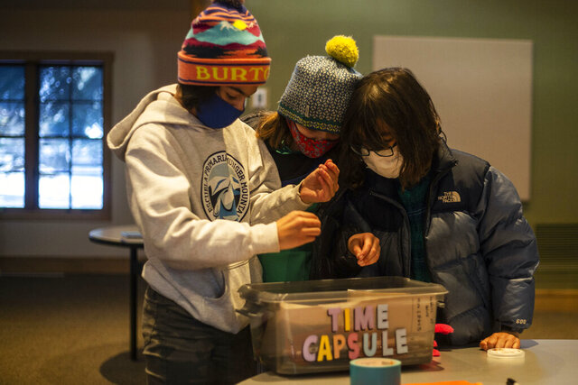 From left to right, Mira Borrego, Anna Baxter and Joy Hayashida-Ludington place items into a time capsule Oct. 26, 2020 at St. John's Episcopal Church in Jackson, Wyo. The book club will return in five years to unearth their capsule. (Ryan Dorgan/Jackson Hole News & Guide via AP)