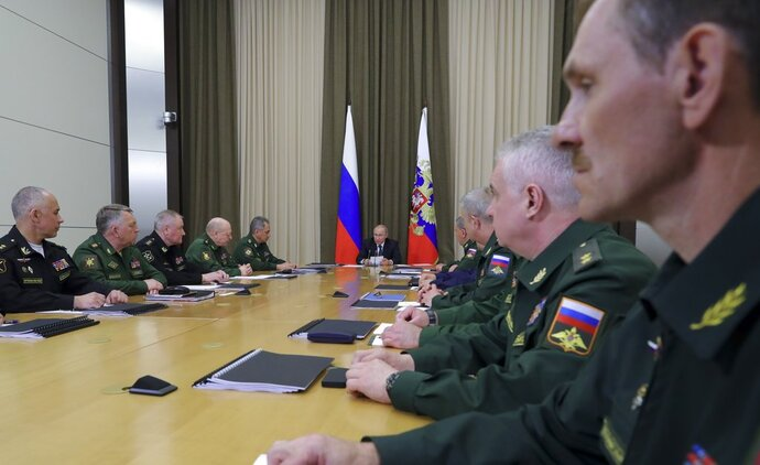 Russian President Vladimir Putin, background center, leads a meeting with the top military brass in the Bocharov Ruchei residence in the Black Sea resort of Sochi, Russia, Tuesday, May 15, 2018. Putin says the new weapons presented this year will ensure Russia's security for decades to come. (Mikhail Klimentyev, Sputnik, Kremlin Pool Photo via AP)