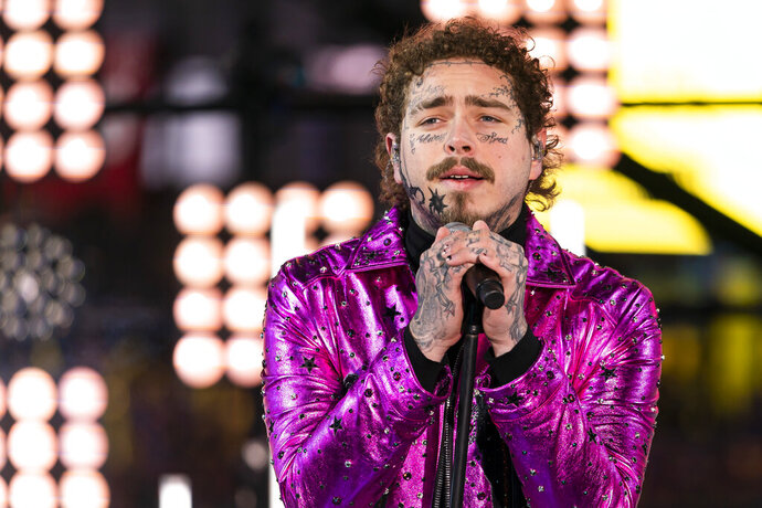 FILE - This Tuesday, Dec. 31, 2019, file photo shows Post Malone performing at the Times Square New Year's Eve celebration in New York. Post Malone is the sunflower of the 2020 Billboard Music Awards. The multi-platinum 25-year-old star scored 16 nominations, dick clark productions and NBC announced Tuesday, Sept. 22, 2020. Malone's nominations include top artist, top male artist, top rap artist and top streaming songs artist.  (Photo by Ben Hider/Invision/AP, File)