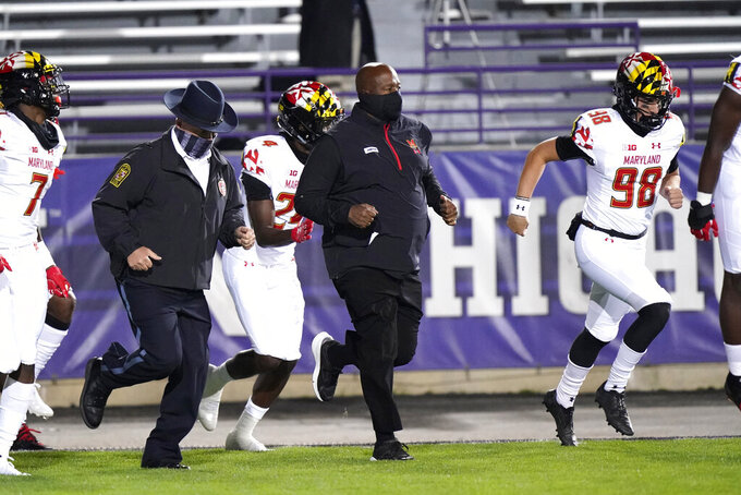 Maryland head coach Mike Locksley, center, runs with players on the field before an NCAA college football game against Northwestern in Evanston, Ill., Saturday, Oct. 24, 2020. (AP Photo/Nam Y. Huh)