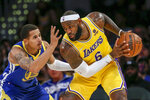 Los Angeles Lakers forward LeBron James, right, is defended by Golden State Warriors forward Juan Toscano-Anderson during the second half of a preseason NBA basketball game in Los Angeles, Tuesday, Oct. 12, 2021. (AP Photo/Ringo H.W. Chiu)