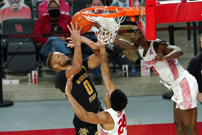 Wichita State's Dexter Dennis (0) is fouled by Houston's DeJon Jarreau (3) as Quentin Grimes (24) helps defend during the second half of an NCAA college basketball game Wednesday, Jan. 6, 2021, in Houston. (AP Photo/David J. Phillip)